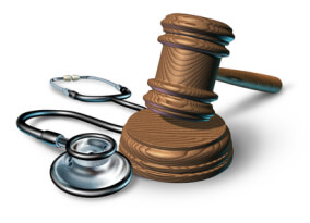 Medical malpractice and the legal proceedings in a work injury concept with a stethoscope and a judge gavel or mallet as a symbol of financial insurance law  issues in health care and medicine on white.